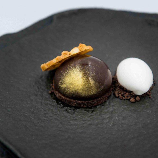 Fermented rice sorbet with a dome of passion fruit and mango, encased in a valrhona chocolate citrus glaze